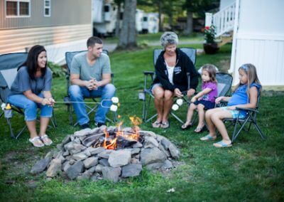 Mom, Dad, Grandmother, and two kids around campfire roasting marshmallows