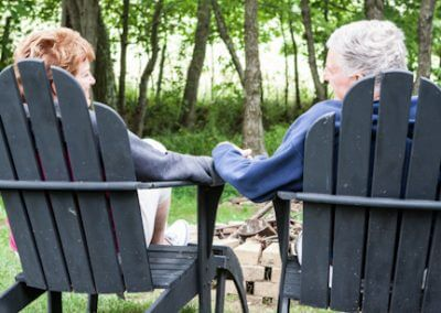 Couple holding hands in adirondack chairs