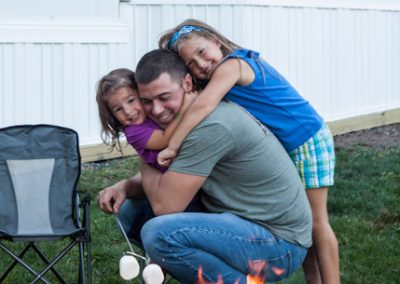 Dad with two daughters hugging him while roasting marshmallows