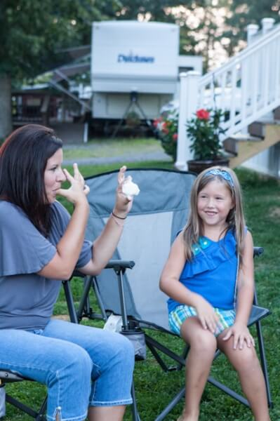 Lady licking fingers with marshmallow in other hand, little girl smiling at her